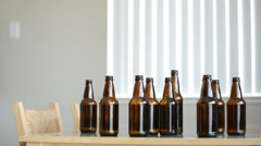 Drunk man sits at table with beer bottles Stock Footage