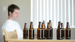 Drunk man is depressed at table with empty bottles Stock Footage