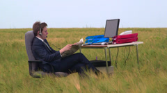 Business person reading newspaper at office desk in a green field Stock Footage