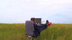 Business man wearing headset at office desk in a green field Stock Footage