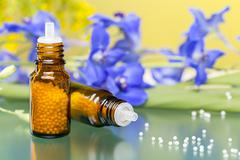 two bottles with homeopathy globules and flowers, with green reflecting under - stock photo