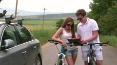 Young couple with bicycles near his car looking at map on tablet computer Stock Footage