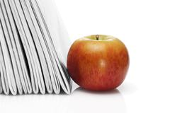 red apple beside pile of school workbooks - stock photo