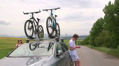 Couple carrying bicycles on the roof of his car Stock Footage