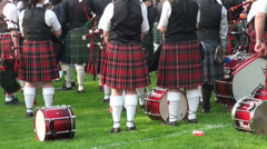 Bagpipe band drummers in kilts waiting at Highland Gathering Stock Footage
