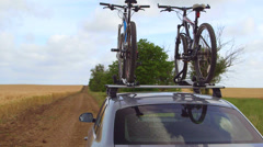 Car with two bicycles mounted on bike roof carrier on a country road Stock Footage