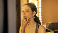 Professional makeup artist uses brush to apply lip gloss to model's lips. Stock Footage