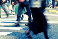 People commuting in rush hour at zebra crossing - stock photo