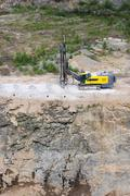 Drilling machine in open cast mining quarry Stock Photos