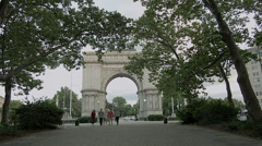 Young people walk from the sailor's arch in Grand Army Plaza, Brooklyn Stock Footage