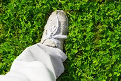feet on a green grass - stock photo