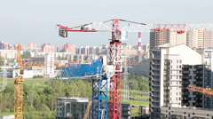 Several cranes over building under construction, agaist cityscape Stock Footage