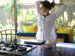 Pretty woman finishing work on laptop, drinking coffee and relaxing at home NTSC - stock footage