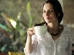 Young woman finishing work on laptop, drinking tea and relaxing at home. NTSC Stock Footage