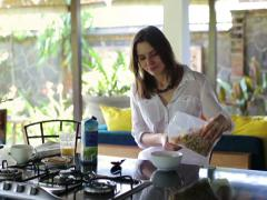 Young, pretty woman pouring cereals with milk in the kitchen at home NTSC Stock Footage