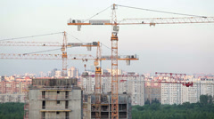 Several cranes over building under construction, agaist sky Stock Footage