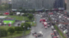 Blurred view of city street through the glass with rain drops, defocusing Stock Footage