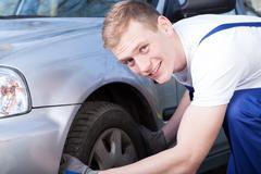 auto mechanic checks a car tire - stock photo