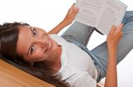 Stock Photo of Brown hair teenager lying down holding book