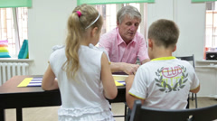 Children sitting in front of granddad and playing domino game - stock footage