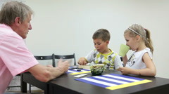 Grandfather talking with grandchildren at the table - stock footage
