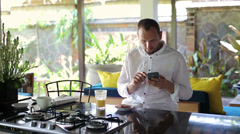 Man texting, using smartphone in beautiful open kitchen HD Stock Footage