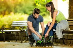 Man helping his girlfriends to put rollerblades Stock Photos