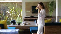 Beautiful woman drink juice and walking in luxury home HD - stock footage
