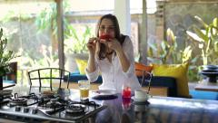 Woman eating sandwich with jam and drinking juice in open kitchen HD Stock Footage