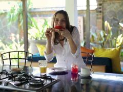 Woman eating sandwich with jam and drinking juice in open kitchen NTSC Stock Footage