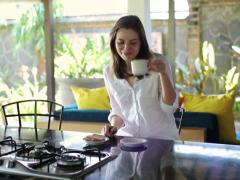 Woman eating snack and drinking coffee in beautiful open kitchen NTSC Stock Footage