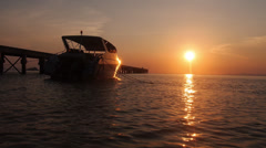 Stock footage boat sea pier sunset orange reflection Stock Footage