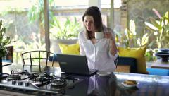 Woman working on laptop and drinking coffee in open kitchen HD - stock footage
