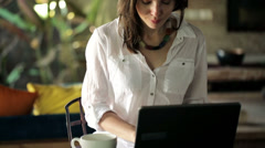 Woman working on laptop and drinking coffee at home HD Stock Footage