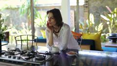 Pensive, sad beautiful woman drinking coffee in open kitchen HD Stock Footage