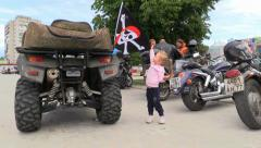 Little Girl watch biker flag with skull and crossbones on ATV Stock Footage