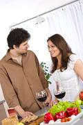 Happy couple drink red wine in modern kitchen Stock Photos