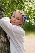 Beautiful young woman lean elbow on the tree Stock Photos