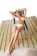Beach - Woman in bikini sunbathing on deck chair - stock photo