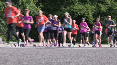 Runners in a marathon race pounding the pavement - stock footage