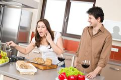 Cooking - happy couple in modern kitchen Stock Photos