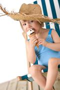Beach - Little girl on deck-chair with hat and ice-cream - stock photo