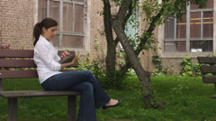 Caucasian woman on a bench in a park with tablet Stock Footage