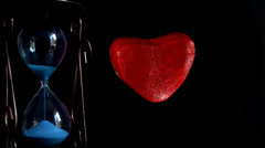 Hourglass next to the dying red heart Stock Footage
