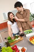 Happy couple cook together in modern kitchen Stock Photos