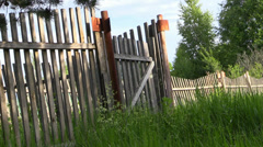 Rustic old rickety wooden fence with a gate and grass - stock footage
