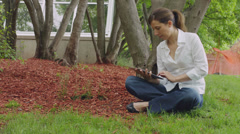 Caucasian woman sitting in the grass park with tablet Stock Footage