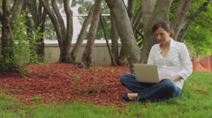 Caucasian woman sitting in the grass park with computer Stock Footage