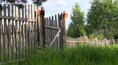 Rustic old rickety wooden fence with a gate and grass Stock Footage