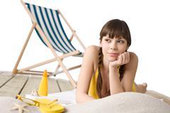 Beach with deck chair - Woman in bikini sunbathing - stock photo